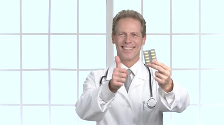 gesture pack : Mature physician showing blister of pills. Smiling middle aged doctor with medical pills gesturing thumb up. Pharmaceutical success concept.