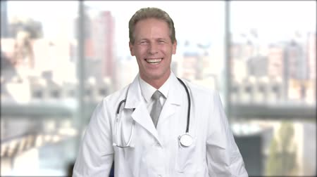 piada : Joyful mature doctor on blurred background. Middle-aged doctor in white coat laughing on window city background. Vídeos