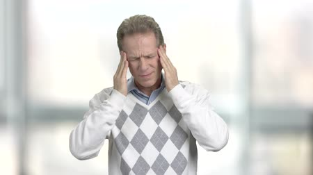 tartás : Mature man suffering from headache. Frustrated mature man touching head with fingers and keeping eyes closed, blurred background.