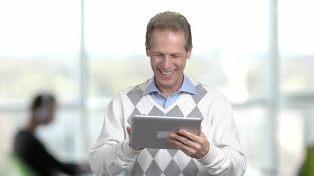 jegyzettömb : Joyful mature man with pc tablet. Happy middle-aged man waving with hand and looking at digital tablet, office window background. People, internet, technology. Stock mozgókép