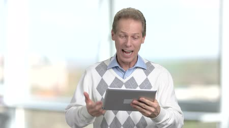 возможность : Mature man using pc tablet. Cheerful caucasian person talking via internet with digital tablet, blurred background. Modern technologies expand the possibilities. Стоковые видеозаписи