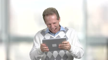 tabuleta digital : Funny man playing on pc tablet. Cheerful mature man playing game on portable gigital tablet, blurred background. Winner of computer game. Stock Footage