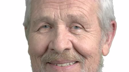 bölcs : Face of elderly man, white background. Close up senior man is smiling, isolated on white background. Cheerful caucasian pensioner close up.