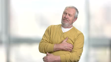 infarct : Senior man with heart attack. Unhappy mature man clutching his chest on blurred background. Heart problem concept.