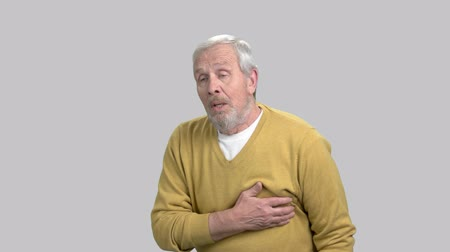 infarction : Unhappy man having chest pain. Portrait of caucasian senior man with heart-attack on grey background.