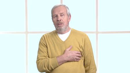 diagnostikovat : Male senior taking a medication. Aged man having discomfort in chest, blurred background. Do not forget about prescription. Dostupné videozáznamy