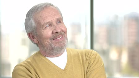 memories : Happy senior man on blurred background. Portrait of cheerful aged man is thinking. Elderly man is dreaming close up. Recollection of happy moments. Stock Footage