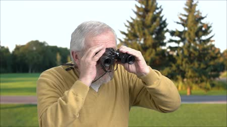 teleskop : Grandfather with binoculars on nature background. Senior man looking through binoculars outdoors. Exploring of summer landscape. Stok Video