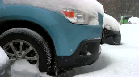 Close up of car wheels stuck in snow drift. Car and falling snow in winter. Winter season concept.