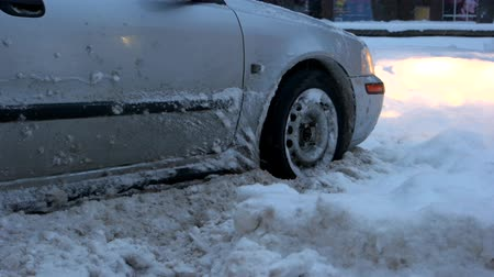 Car stalled in the snow. Close up of car wheel stuck in snow drift. Did you buy winter tires? Стоковые видеозаписи