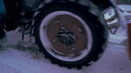 Close up tractor cleaning snow from road. Wheel tractor removing snow from the road after heavy snow fall. Bad weather conditions. Winter road cleaning service. Стоковые видеозаписи