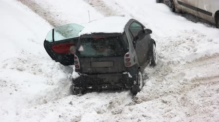 Car stuck in ther snow after snow fall. Driver digs out car with shovel. Snow causes traffic problems.