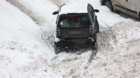 Car driving in adverse weather conditions. Urban street after heavy snowfall. Winter driving safety tips.