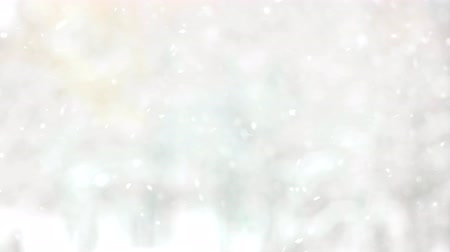 Blurred gray winter background. Falling snow and snowflakes. Winter fairy tale.