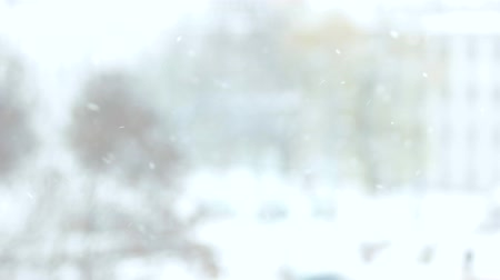 Close up falling snow. Blurred background of snowfall in the town. Winter time concept.
