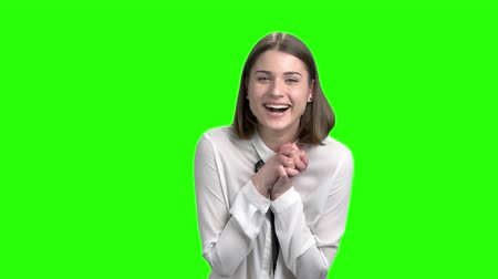 Happy girl with folded hands laughing, slow motion. Green screen hromakey background for keying.