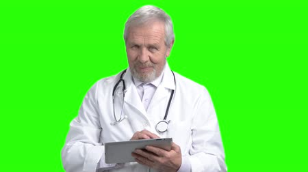 Old smiling doctor use tablet. Portrait of old man chatting and typing using electronic device. Green screen hromakey background for keying. Wideo