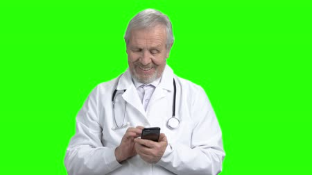 hanedan arması : Portrait of physician typing on smart phone. Green screen hromakey background for keying. Stok Video