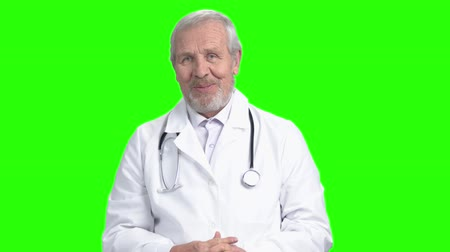 Portrait of old senior doctor talking with folded hands. Green screen hromakey background for keying.