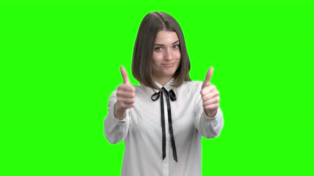 Portrait of brunette teenage girl shows thumbs up. White business shirt. Green screen hromakey background for keying. Wideo