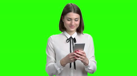 Portrait of teen girl chatting on her smartphone using messangers. Green screen hromakey background for keying.
