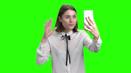 Talking with someone by smartphone web cam. Cute brunette girl. Green screen hromakey background for keying.