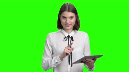 Young female business speaker with tablet. Young cute brunette girl in white blouse. Green screen hromakey background for keying.