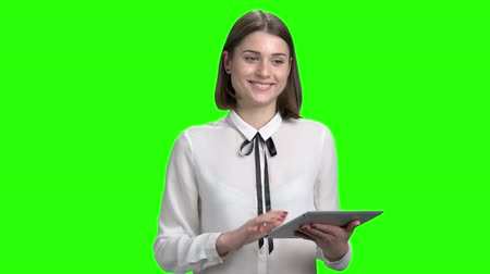 Portrait of young businesswoman with tablet. Teen female teacher. Green screen hromakey background for keying. Wideo