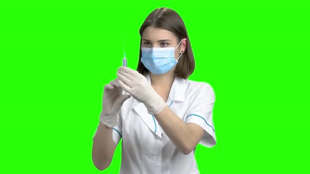 иммунизация : Young female doctor with syringe. Woman physician in protective mask portrait. Green screen hromakey background for keying.