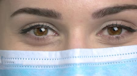 Macro view, female doctor eyes closing. Blinking eyelashes. Protective mask.
