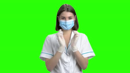 Portrait of young female doctor put on gloves. Green screen hromakey background for keying.