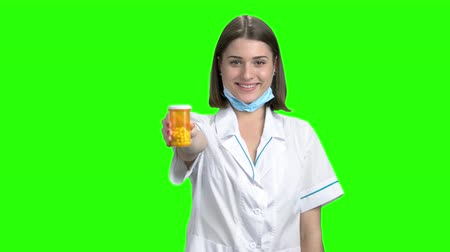 продвигать : Can of pills and thumb up. Teen breunette girl working as doctor and promote medicines. Green screen hromakey background for keying.