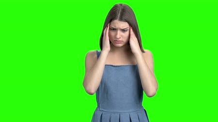 Teen female having headache. Touching head, feeling pain. Green screen hromakey background for keying.