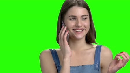 Beautiful brunette woman talking on phone with her boyfriend. Teen girl having small talks on the phone. Green screen hromakey background for keying.