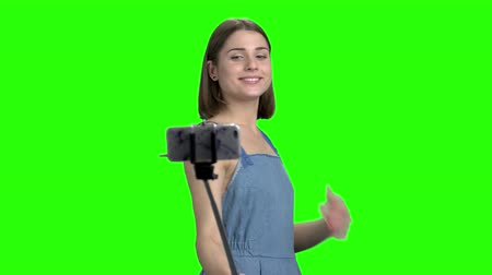 Posing for instagram photo. Cute girl making photo using smartphone and selfie stick. Green screen hromakey background for keying.