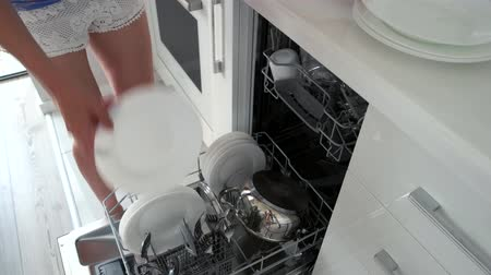 Woman unloading dishwasher, fast motion. Open dishwasher with clean utensils. How to unload dishwasher quick.