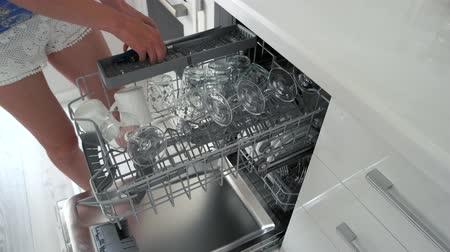 Woman taking out clean dishes from dishwasher machine. Housewife unloading clean knives and glasses from dishwasher at home. Home equipment for cleaning.