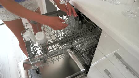 Woman loading glasses and glassware to dishwasher machine. Dishes cleaning process. People, chores and technology. Wideo