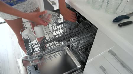 Woman unloading the dishwasher at home. Housewife doing home chores. Modern equipment for dishes cleaning.