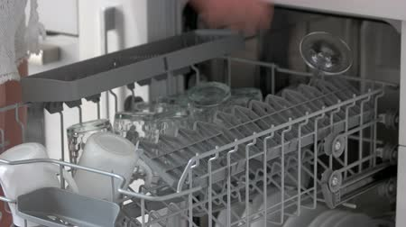 Female hands unloading dishwasher at home. Open dishwasher with clean dishes close up. Household chores concept.