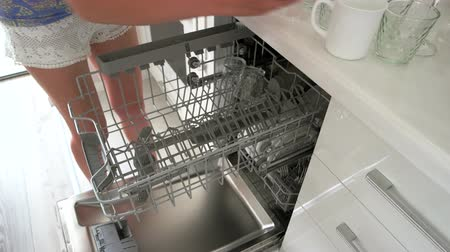 Woman putting glass in the dishwasher at home. Young woman filling dishwasher with glassware at home kitchen. How to stack dishwasher.