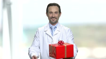 bonus : Handsome male doctor offering gift box. Smiling man in white robe giving present box on blurred background. Stock Footage