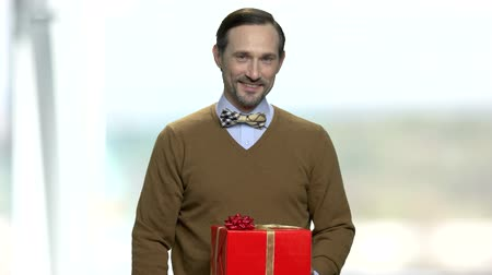 intrigue : Handsome man offering gift box. Attractive smiling man giving present box, front view. Holiday sales concept.