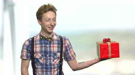 bonus : Smiling boy offering gift box. Cute teenage boy giving present box. Gifts delivery concept. Stock Footage