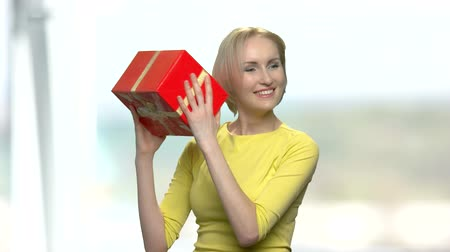 Young excited woman with red gift box. Happy surprised woman holding gift box on blurred background.