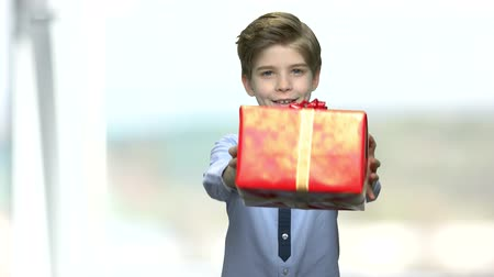 Cute happy boy in shirt with gift box. Handsome little boy stretching out gift box and looking at camera on blurred background.