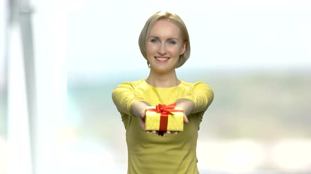 intrigue : Woman handing gift box. Young pretty blonde girl with present box on blurred background. Give joy for your close people.