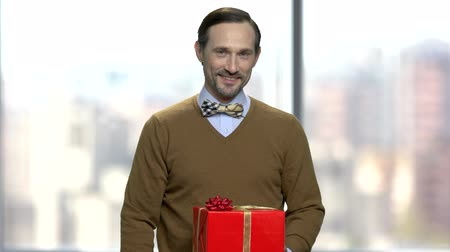 intrigue : Smiling caucasian man giving gift box. Attractive man with bow-tie holding large gift box and looking at camera. Gift for special event.
