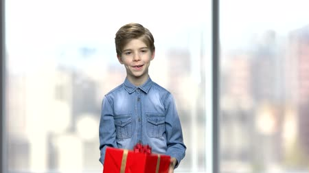 Boy playing with gift box. Cute kid with gift box on blurred background. Holidays are coming.