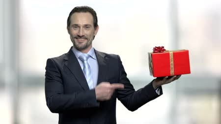 prêmio : Handsome man presenting gift box. Elegant smiling businessman pointing with finger on beautiful gift box. Get holiday bonus concept.